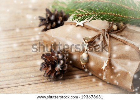 Christmas packed present with x-mas tree branches and pine cones - stock photo
