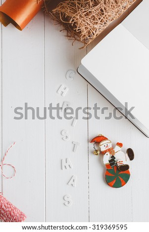 Christmas paper, ribbons and decorations along with a notepad on a white wooden table. - stock photo