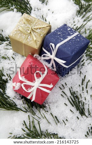 Christmas parcels on snow-covered fir branch, close up - stock photo