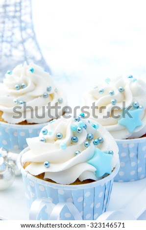 Christmas party cupcakes with white frosting and baby blue decorations  - stock photo