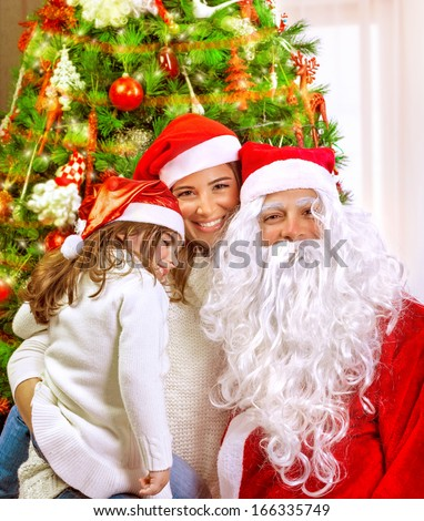 Christmas party, happy family at home celebrating New Year, mother with daughter and Santa claus near Xmas tree, happiness concept - stock photo
