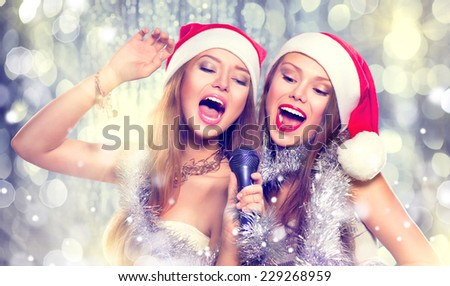 Christmas party, karaoke. Beauty girls in santa hat with a microphone singing and dancing over holiday blinking background. Disco. New year celebration - stock photo