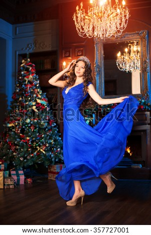 Christmas party, winter holidays woman with gift box. New year girl. christmas tree in interior background.