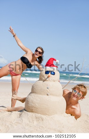 Christmas people on beach with snowman made out of sand wearing sunglasses. - stock photo