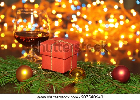 christmas photo cognac glass and gift box in front of bokeh background.