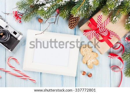Christmas photo frame on wooden table with tree, camera and gift box. Top view with copy space - stock photo