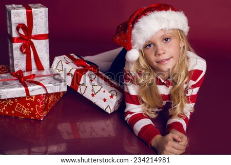 Christmas photo of little cute girl 9 years old wearing Santa hat and holding big present box - stock photo