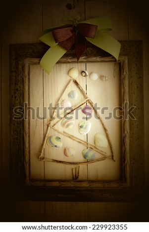 Christmas picture,Christmas tree made with shells painted by children and sticks - stock photo