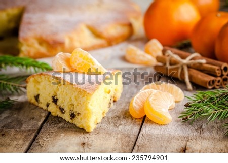 Christmas piece of biscuit cake with mandarin oranges and cinnamon on a rustic background - stock photo
