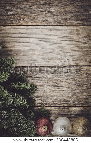 Christmas Pine Needle and Ornaments on a Rustic Wood Background - stock photo
