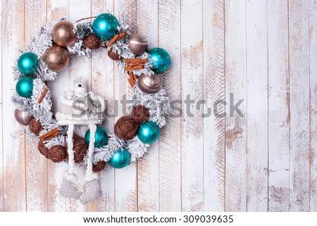 Christmas pine wreath is hanging on the human door. A toy animal is sitting on the decoration. Copy space in right side - stock photo