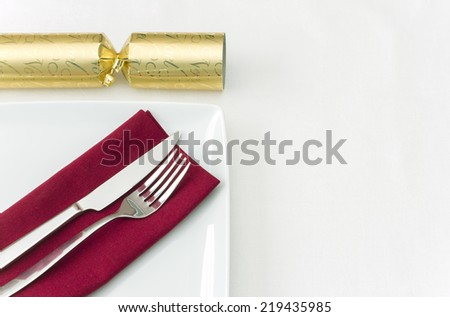Christmas place setting with gold cracker - stock photo