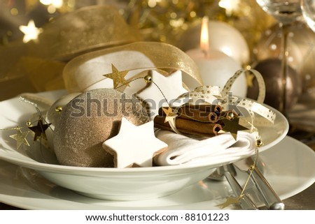 christmas place setting with gold ribbon and decoration - stock photo