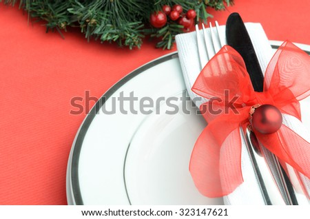 Christmas place setting with red ribbon and bauble  - stock photo