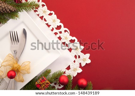 Christmas place setting with ribbon and christmas decorations - stock photo