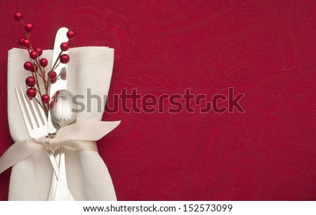 Christmas Place Setting with Sterling Silverware in White Napkin and Ribbon on Red Background with Copy space or Room for Your Text or Words. - stock photo