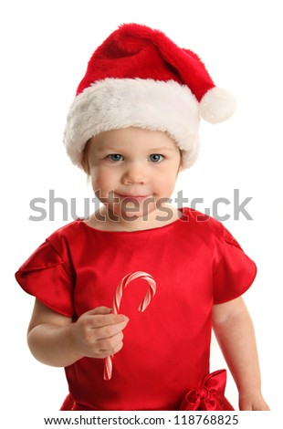Christmas Portrait of a beautiful little child girl wearing a santa hat and holding a candy cane - stock photo