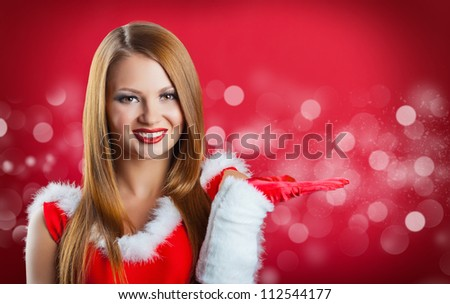 Christmas portrait of a beautiful young woman with bright make-up showing empty hand  on a red background