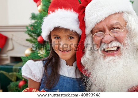 Christmas portrait of a girl with Santa Claus smiling - stock photo