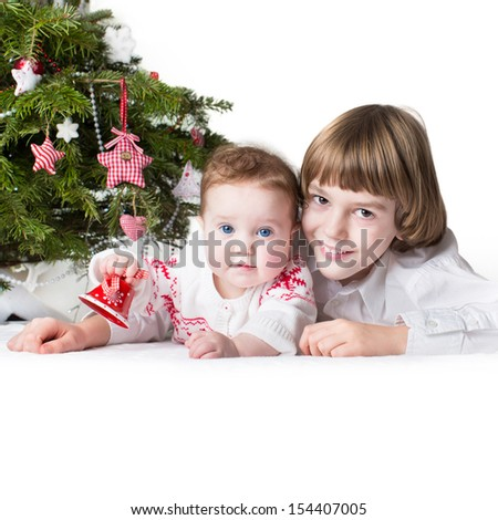 Christmas portrait of a little boy and his adorable baby sister under a decorated tree holding a red and white bell - on white background, square - stock photo