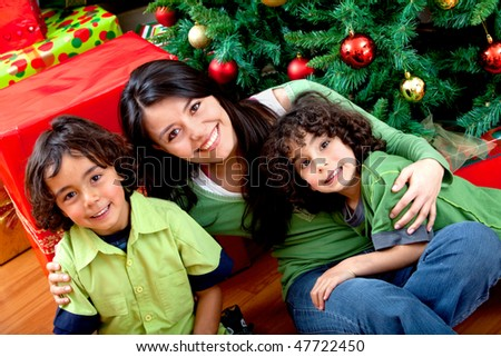 Christmas portrait of a woman with two boys smiling - stock photo