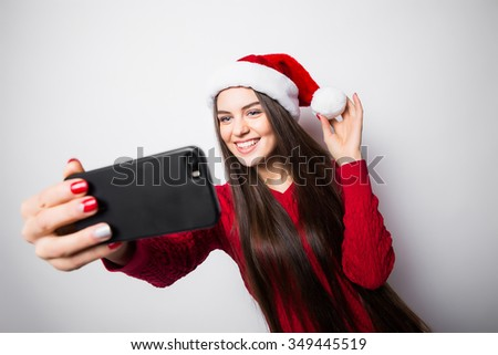 Christmas portrait of beautiful girl. Teenager wearing santa claus hat. Girl smiling and making selfie on mobile phone - stock photo