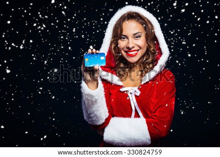 Christmas portrait of beautiful mixed-race santa girl. Young sexy brunette woman wearing santa claus clothes. Snow Maiden holding credit card on black background with snow  - stock photo