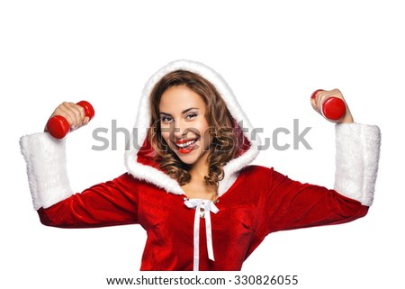 Christmas portrait of beautiful mixed-race santa girl. Young sexy brunette woman wearing santa claus clothes. Snow Maiden holding red dumbbells on white background - stock photo