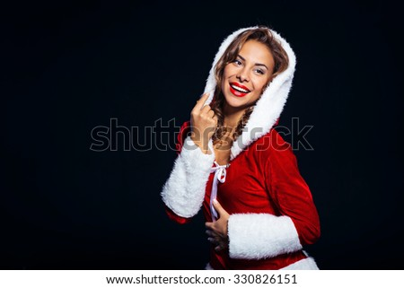 Christmas portrait of beautiful mixed-race santa girl. Young sexy brunette woman wearing santa claus clothes. Snow Maiden smiling on black background - stock photo
