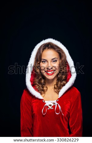 Christmas portrait of beautiful mixed-race santa girl. Young sexy brunette woman wearing santa claus clothes. Snow Maiden cheerfully smiling on black background - stock photo