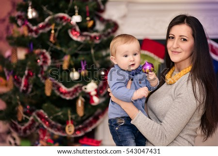 Christmas portrait of mother and little son in a cozy atmosphere around the fireplace and Christmas tree