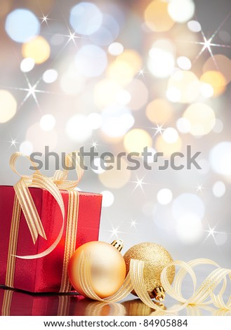 christmas present and baubles against bokeh lights background - stock photo