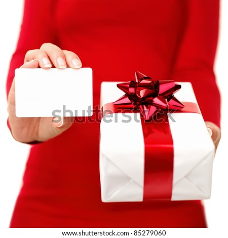Christmas present and gift card. Woman holding gift card or business card while showing christmas present. Red and white colors. Closeup isolated on white background. - stock photo
