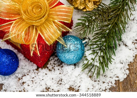 Christmas present and ornaments on snow. - stock photo