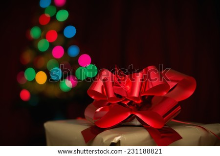 Christmas present, christmas tree and red satin in the backround - stock photo