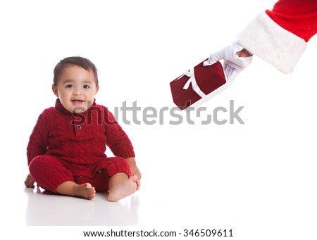 Christmas Present from Santa. Adorable mixed race baby boy receiving a Christmas Present from Santa. - stock photo