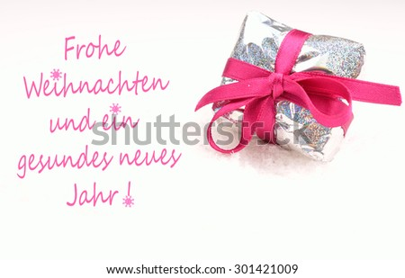 Christmas present in silver with a pink bow on a white snow background, German Merry Christmas background - stock photo