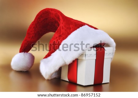 Christmas present with santa hat close up - stock photo