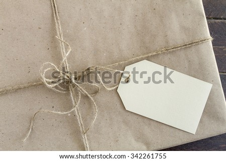 Christmas present wrapped in brown wrapping paper with brown burlap twine tied in a bow and blank tag sitting on wooden table - stock photo