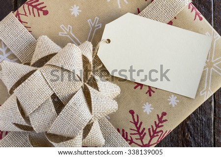 Christmas present wrapped in brown wrapping paper with snowflakes, brown burlap bow and blank tag sitting on wooden table - stock photo
