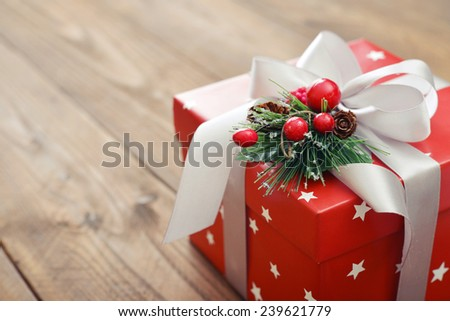 Christmas present wrapped in decorative wrapping paper with ribbon close up - stock photo