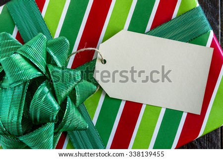 Christmas present wrapped in red and green striped wrapping paper with shiny green bow and blank tag sitting on wooden table - stock photo