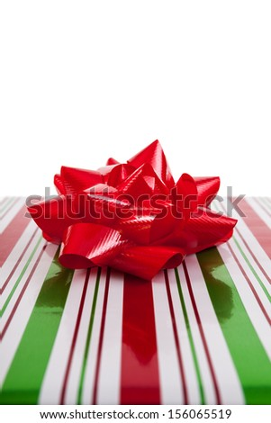 Christmas present wrapped with red and green paper and red bow isolated on white background - stock photo