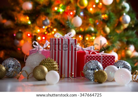Christmas presents and balls against the backdrop of a festive Christmas tree - stock photo