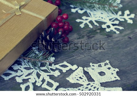 Christmas presents and white knitted snowflakes and angel on a rustic wood background with tone