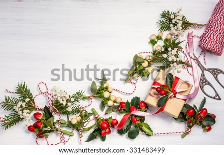 Christmas presents and winter natural garlands on the white wooden background - stock photo