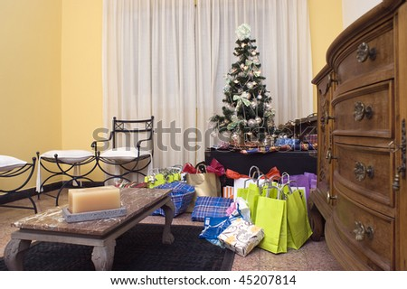 Christmas presents by a tree in a living room. - stock photo