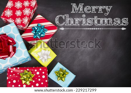 Christmas presents grouped around a chalkboard with Merry Christmas written on it. - stock photo