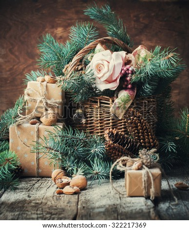 Christmas Presents in Vintage Style. Boxes Decorated with Cord, Basket with Coniferous and Fir Tree Toys, Walnuts, Almonds on Wooden Background - stock photo