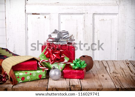 Christmas presents spilling out of a stocking on wooden plank with antique door panel background - stock photo